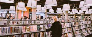 Chica cogiendo libro en una biblioteca